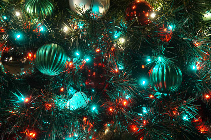 A close up o a Christmas tree decorated with multicolored baubles and Christmas lights