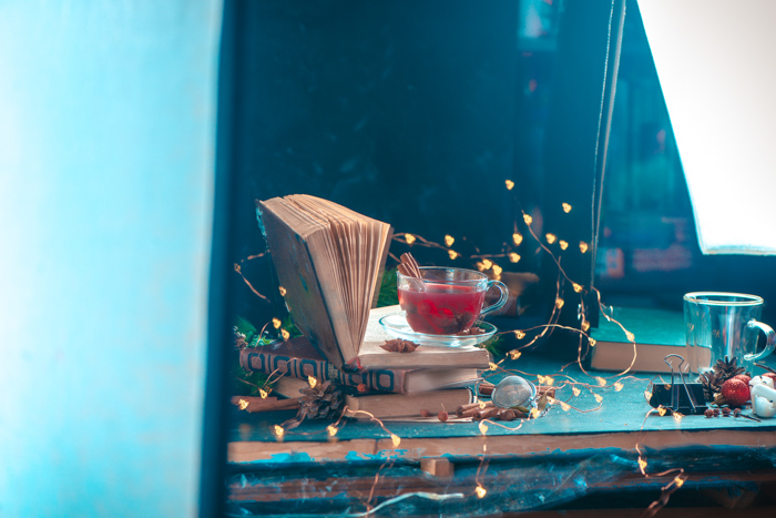 Setting up a magical Christmas still life including an old book, hot drink and Christmas lights