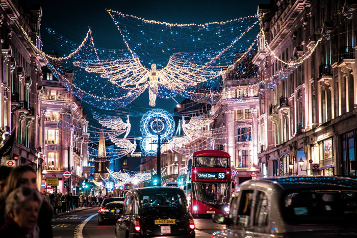 A busy London street scene at night, full of Christmas lights and decorations