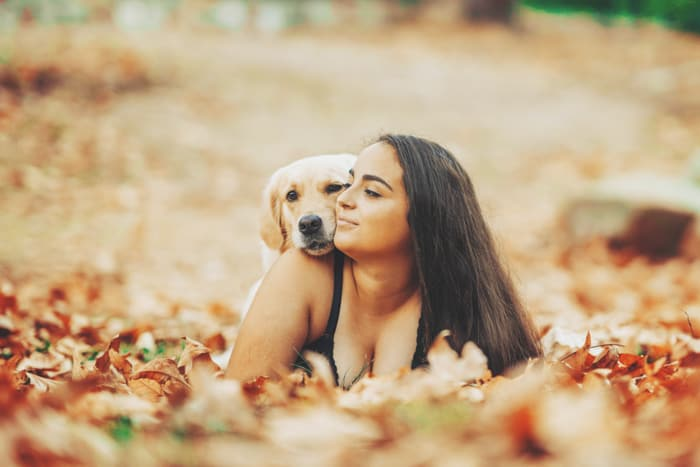 Casual portrait of a female model posing with a dog in autumn leaves - how to copyright photos
