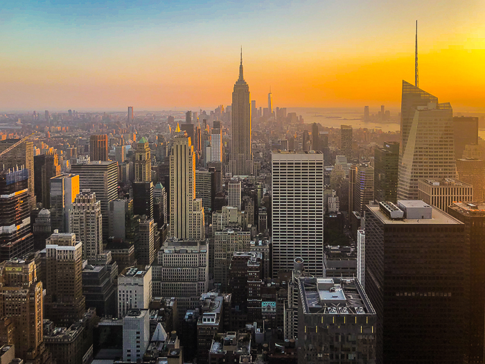 An aerial view of a sprawling cityscape under dramatic skies at sunset