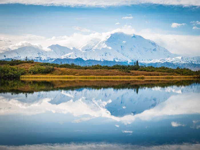 A clear fall landscape shot of snowy mountains reflected in water below