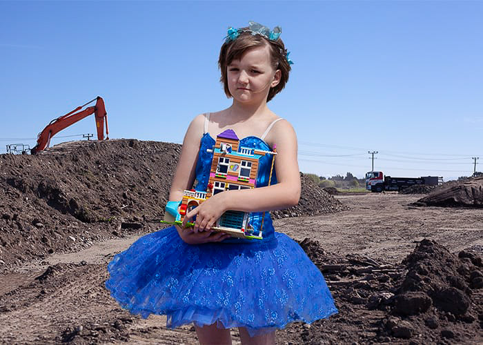 A little girl in blue dress in front of a construction site