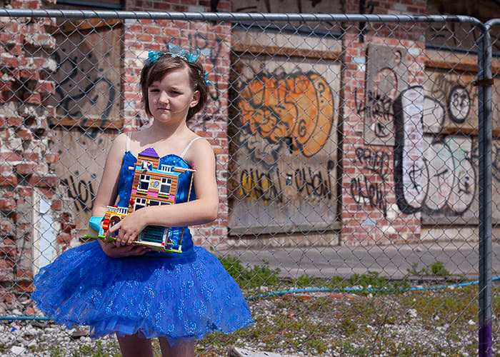 Portrait of a little girl in blue dress in front of a graffiti-ed building