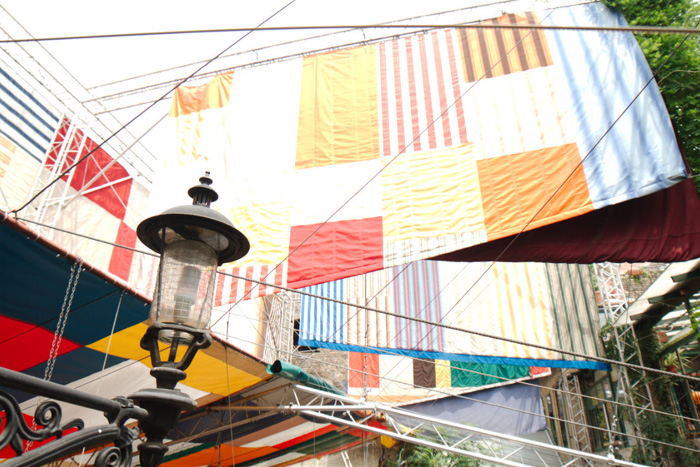Flags and textiles hanging above a street