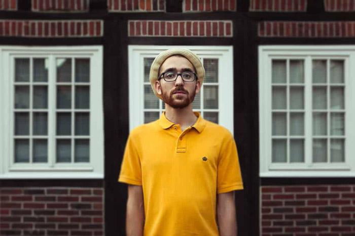 Una fotografía en color de un modelo masculino en camiseta amarilla posando al aire libre