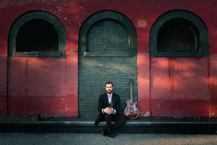 Un retrato en color de un músico posando delante de una pared roja en Brooklyn