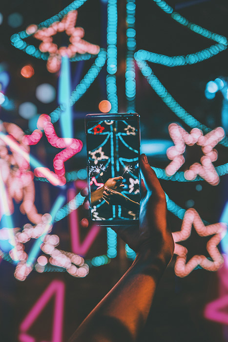 A person taking a smartphone shot of beautiful bokeh effect Christmas lights