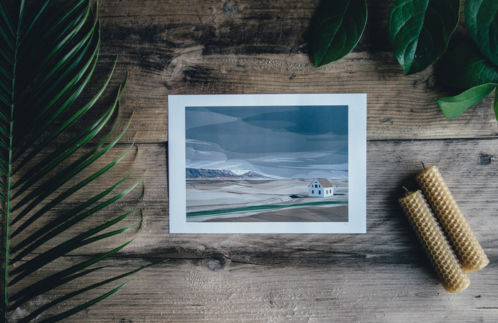 A flat lay of a landscape photo print and foliage on a wooden table