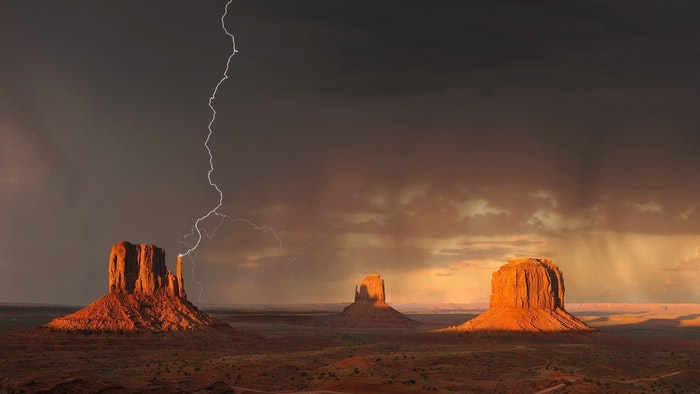 Forked lighting striking over a desert landscape at night