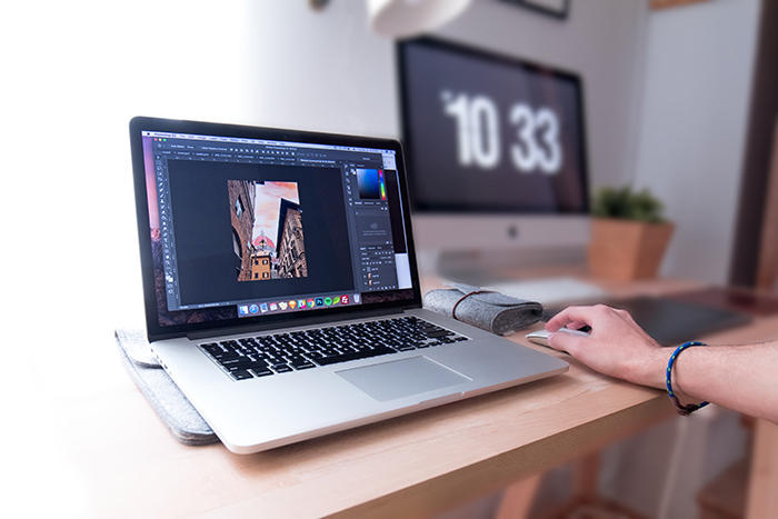 A person editing photos on Lightroom 6 in a home office
