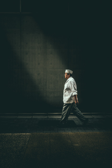 A street photography portrait of a man in chefs uniform walking down a street in low light