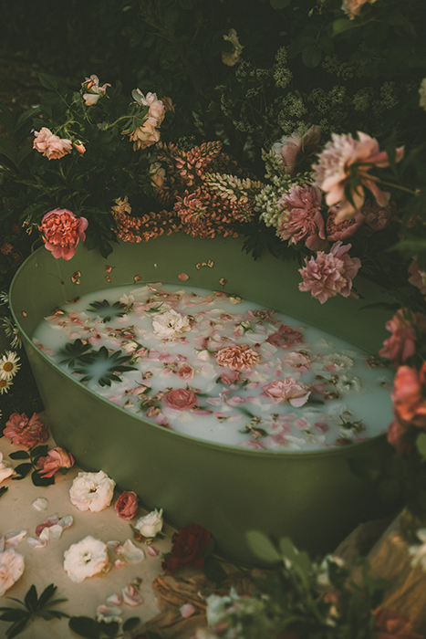 A milk bath strewn with flowers and petals