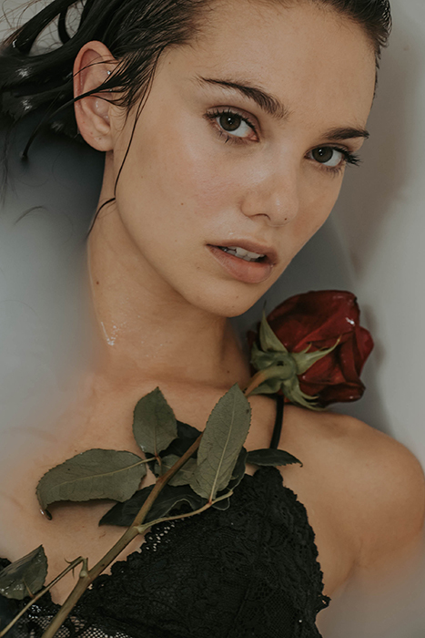 Beautiful milk bath photography close up of a female model holding flowers