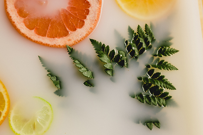 A close up Milk bath photography shot of citrus fruits and leaves in milk