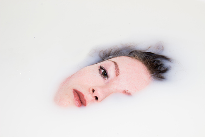 A close up Milk bath photography portrait of a female model submerged in milk
