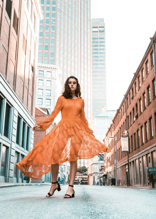 Woman in an orange dress, her hands out and face looking towards the camera in a casual pose