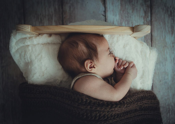 A portrait of a newborn in a small bed
