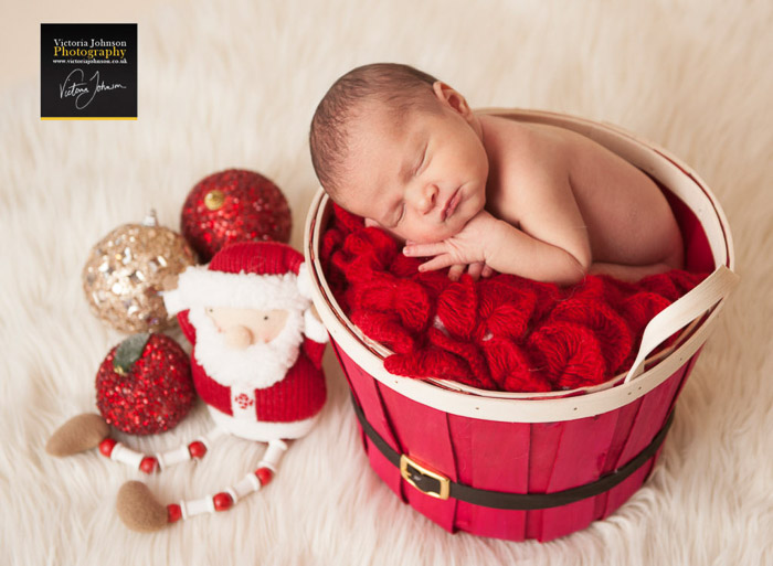 A newborn in a red basket surrounded by Christmas themed newborn photography props
