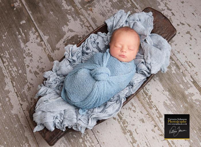 A newborn baby swaddled in blue cloth