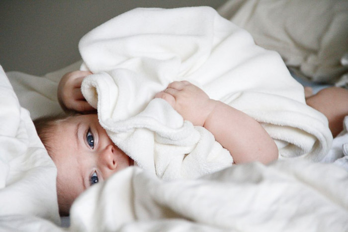 A newborn baby posed in white blanket