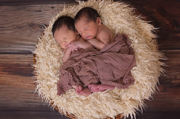 Two newborn babies posed on a rug