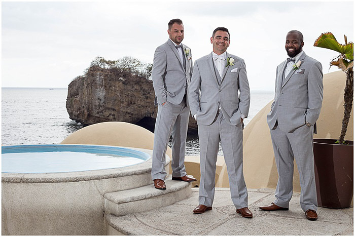 Casual wedding portrait of three groomsmen posing outdoors at a destination wedding
