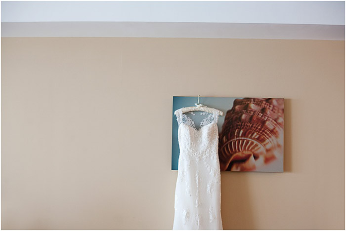 A wedding dress hanging from a mounted photo print - destination wedding tips