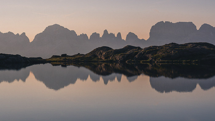 A stunning mountainous landscape over Dolomiti di Brenta relected in the lake below - reflections in photography