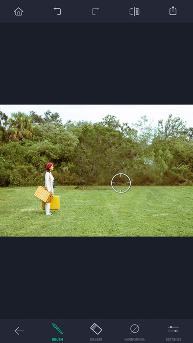 Screenshot of the touch retouch app, a woman with red hat and yellow bags standing on the field, with the brush tool visible