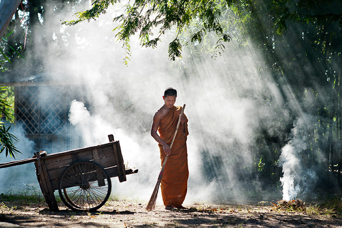 Beautiful rim light portrait of a Buddhist monk sweeping outdoors