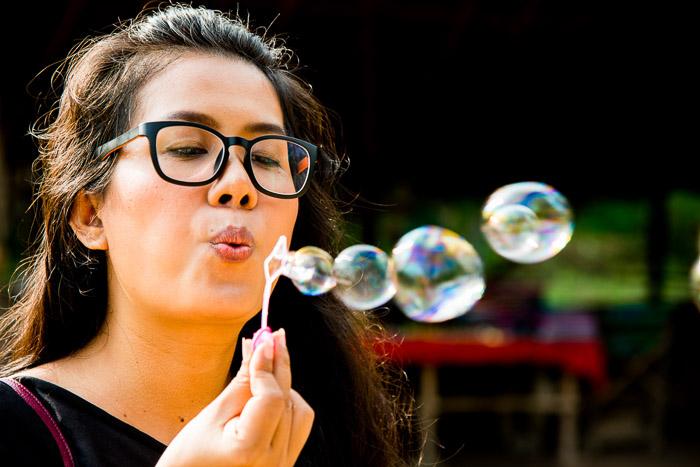 A portrait of a female model shot blowing bubbles
