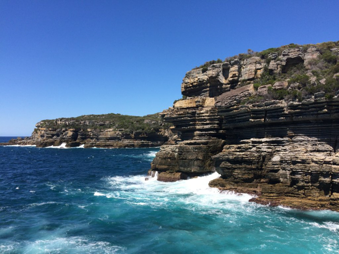 turquoise waters and foamy waves crashing against a rocky cliff face against a bright blue sky - photo editing tips for smartphone photography