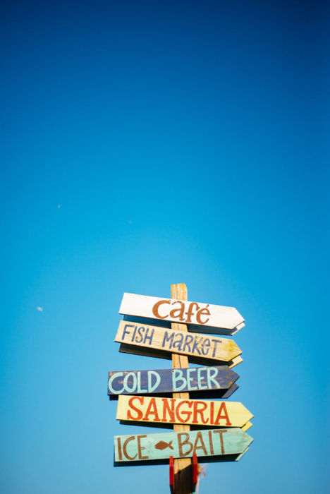 hand-painted signs on a wood post against a clear bright blue sky