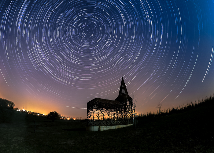 Silhouette of the See Through Church lit warmly from behind, under the star filled night sky