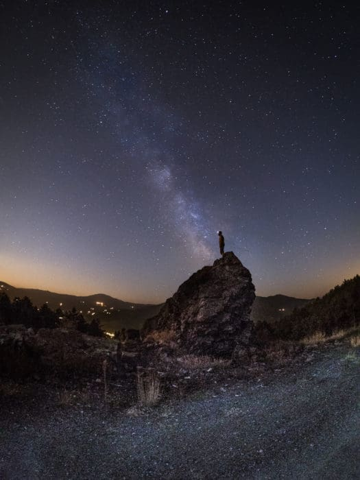 A man on a rock under the Milky Way.