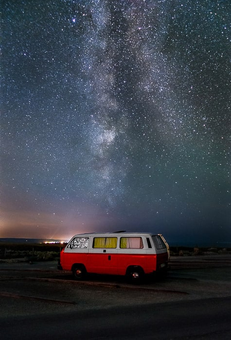 A van parked right in front of the Milky Way.