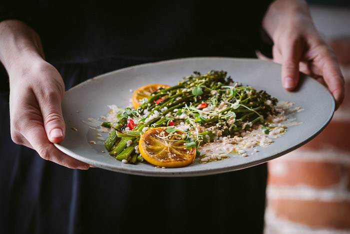 Food photography shot of a person holding a plat of salad and rice
