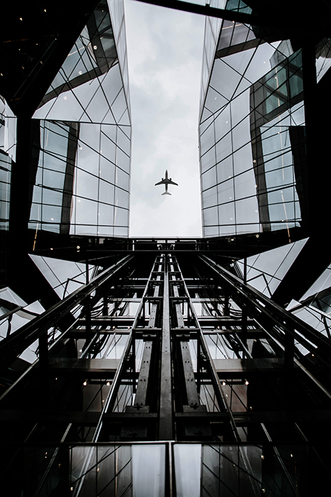 Interesting composition of an airplane framed by a multilayered glass building