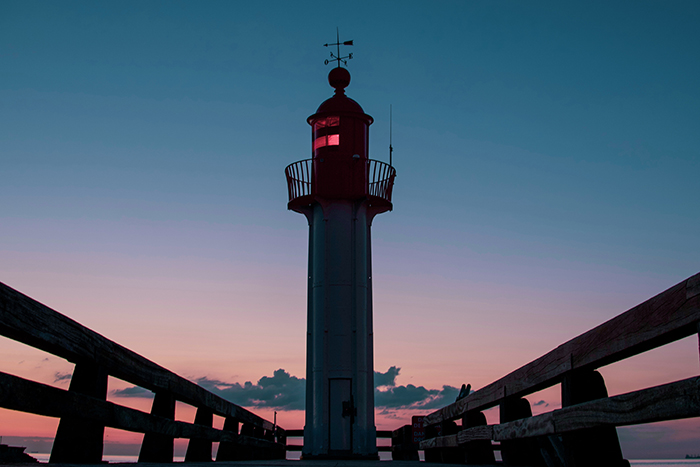A symmetrical photo of a lighthouse at evening time