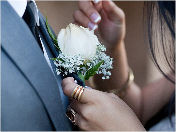 Close up prom photography of a cute couple pinning a corsage onto a suit