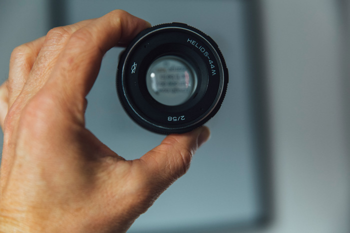 A person holding up a camera lens to an opticians eye chart - autofocus issues