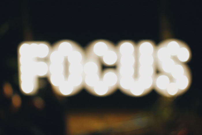 A blurry image of a neon sign reading 'focus'