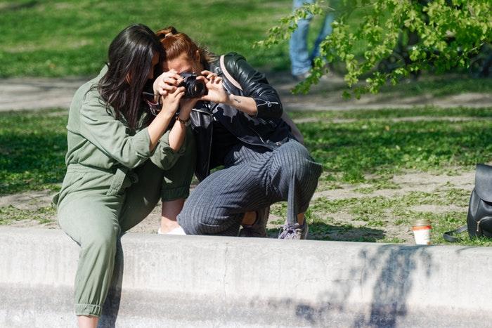 Dos mujeres en un parque mirando una cámara DSLR