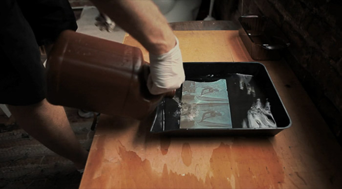 A close up of a photographer demonstrating the wet plate photography process