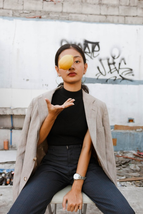 Woman throwing a lemon in the air, looking towards the camera in a casual pose