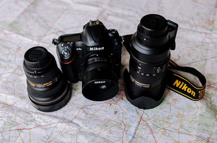 A Nikon camera and lenses resting on a map