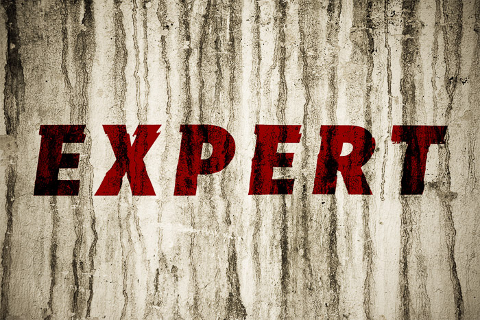 A textured grunge wall with the word 'expert' in red - using displacement map photoshop