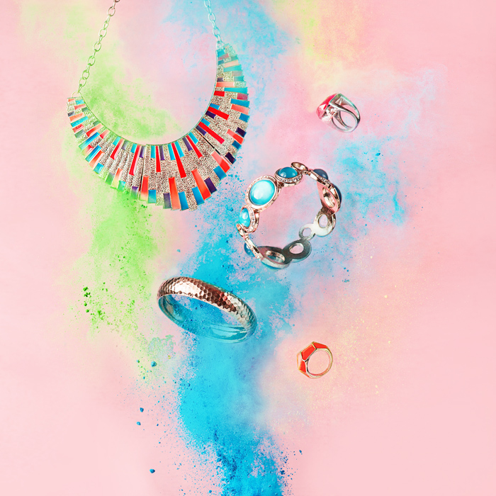A magical still life shot using jewellery and colored flour clouds