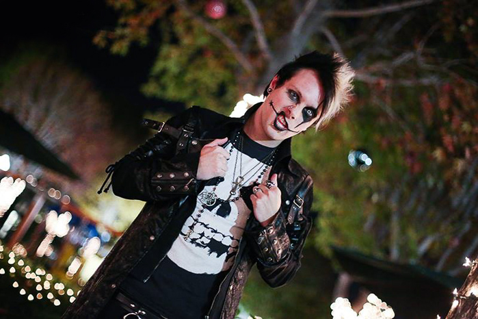 A male model in goth gear posing for night portrait photography